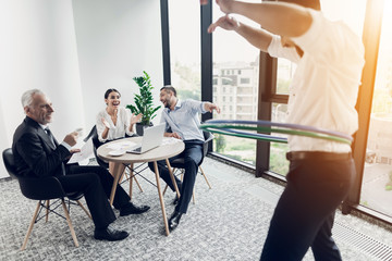 Businessman in the office turns hula-hoop. His colleagues sit at the table and look at him. They are very fun