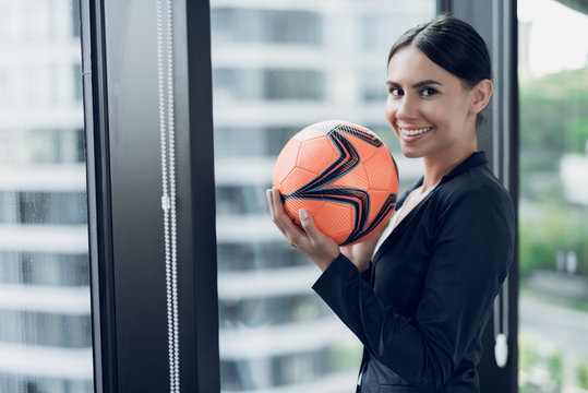 A woman in a strict business suit holds an orange football in her hands. She smiles