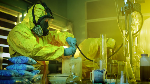 In the Underground Drug Laboratory Two Clandestine Chemists Wearing Protective Masks and Coveralls Use Hosepipe For Drug Distillation.