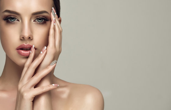 Beautiful model girl with a beige French manicure nail design with rhinestones . Fashion makeup and care for hands and nails and cosmetics