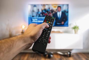 Fernsehen mit Fernbedienung in der Hand