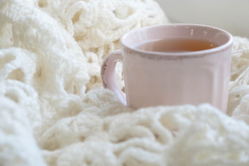 Warm and comfy autumn or winter concept. Book, cup of lemon tea and sweater on wooden window sill in old house. Reading and relaxing in cold fall weather at home. Quiet silent homely scene.