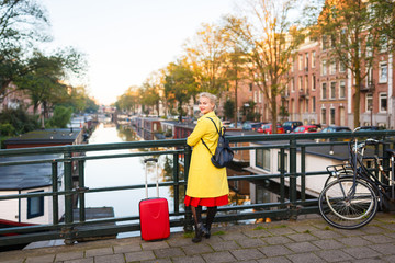The traveler with suitcase is walking in the street of Amsterdam city in autumn
