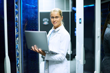 Portrait of young woman wearing lab coat and holding laptop smiling at camera while working with supercomputer in server room