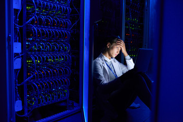 Portrait of tired young woman sitting on floor in dark server room using laptop while working with supercomputer at night
