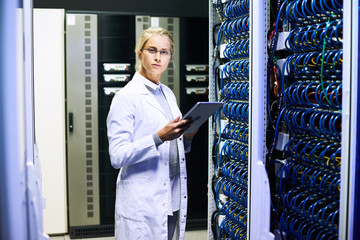Side view portrait of young woman wearing lab coat  looking at camera while working with supercomputer