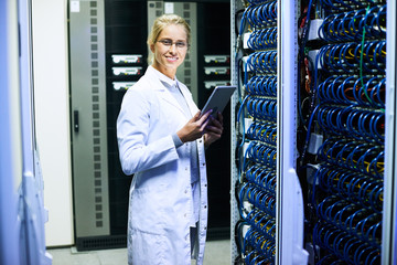 Portrait of young woman wearing lab coat  smiling at camera while working with supercomputer