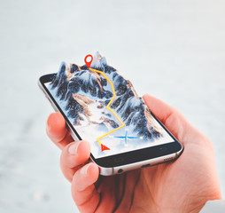 Man holding smartphone with mountains on the screen.