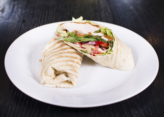 Burrito with grilled chicken and vegetables. Shawarma from juicy beef, lettuce, tomatoes, cucumbers, paprika and onion in pita bread.