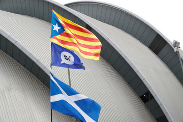 Demonstrators fly the Scottish and Catalan flags outside the conference centre during the Scottish National Party conference in Glasgow
