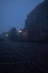 Misty street in old village with illuminating lanterns.