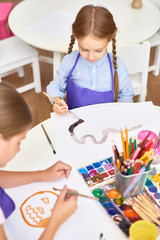 High angle portrait of two girls painting pictures on Halloween enjoying art lesson in development school