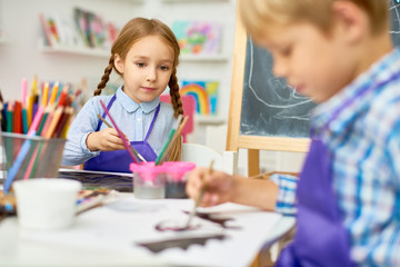 Portrait of adorable little girl  painting pictures enjoying art class in pre school working together with boy
