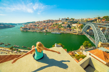 Carefree woman with open arms looking picturesque Porto and Ribeira district skyline. Aerial view of Dom Luis I Bridge on Douro River, Vila Nova de Gaia, Portugal. Female tourist enjoying in sunny day