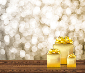 Golden gift box on wood table top with blur sparkling gold bokeh abstract background,panoramic banner for display or montage of product,Holiday seasonal concept backdrop.