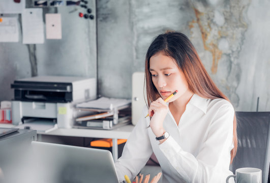 Asian businesswoman thinking with pencil and looking down to laptop computer screen for planning work in office,Office lifestyle concept