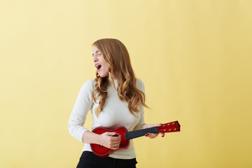 Attractive emotional young Caucasian woman in roll neck sweater singing passionately and playing ukulele. Beautiful woman singer playing musical instrument indoors. People, music, joy and fun