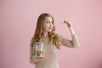 Isolated picture of playful charming young female looking at camera with sly expression and holding jelly bean, gummy bear or marmalade, taking it to her mouth as if teasing you. Candy, sweets