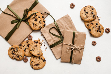 Fond of sweets and gifts for holidays. Small elegant presents on white table with homemade chocolate scones nearby, top view picture