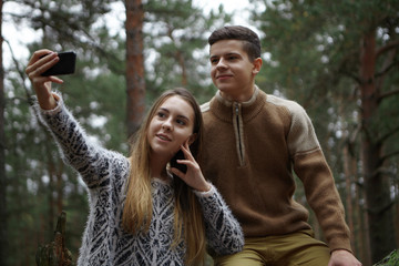Happy siblings sister and brother taking selfie on mobile while hiking in woods. Beautiful young female holding smart phone, taking self portrait, posing in wild nature together with her boyfriend