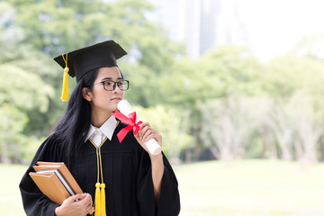 Happy graduate young Asian woman in cap and gown holding a book and certificated in hand, Education concept