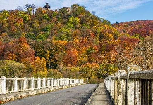Nevytsky Castle, Ukraine - October 27, 2016: bridge to Nevytsky Castle hill with yellow foliage in autumn forest. popular tourist attraction