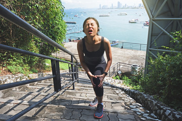 Woman crying for a painful knee injury while exercising and running.
