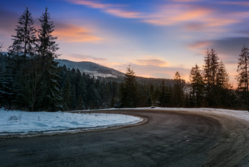 serpentine in winter mountains at sunset. gorgeous landscape with dark spruce forest on hillsides and red clouds on a blue evening sky. lovely transportation scenery of descend road turnaround