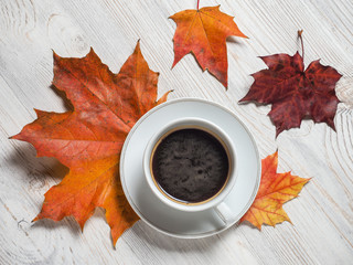 Autumn, autumn maple leaves, a hot Cup on the background of wooden table. Seasonal, morning coffee, Sunday rest and the concept of still life.