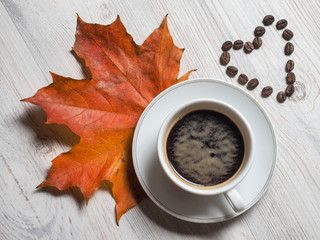 Autumn, autumn leaf of maple with a hot Cup of coffee and heart of coffee beans on the background of wooden table. Seasonal, morning coffee, Sunday rest and the concept of still life.