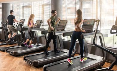 Gruppe von vier Leuten beim jogging auf dem Laufband im Fitnessstudio