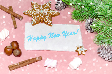 Christmas greeting card over wooden light pink table with snow fir tree, snowflakes, nuts, marshmallow and cinnamon. Flat lay slyle