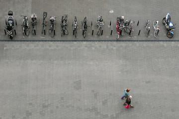 Vogelperspektive auf eine Reihe von geparkten Fahrrädern und Motorrädern und zwei Fußgänger
