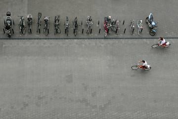 Vogelperspektive auf eine Reihe von geparkten Fahrrädern und Motorrädern und zwei Radfahrer
