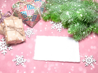Christmas greeting card over light pink table with snowflakes, gifts, fir tree branches. Flat lay style