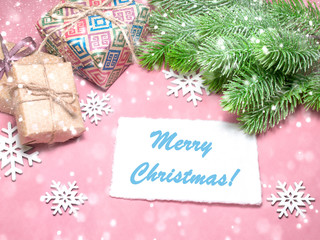 Christmas greeting card over light pink table with snowflakes, gifts, fir tree branches. Flat lay slyle