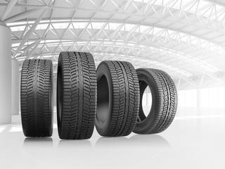 Set of four car tires at big warehouse.