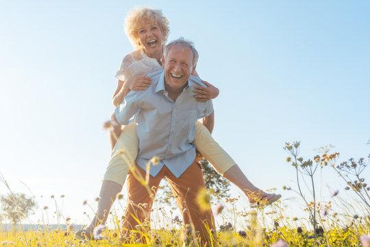 Senior Mann trägt seine Frau auf dem Rücken, er hat eine gesunde Wirbelsäule