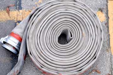 On the asphalt road is a roll of fire-resistant fire hose