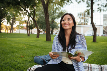 Portrait of young smiling asian woman with book sitting in park, looking aside, outdoor