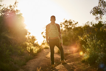 male millennial hiker trekking up trail in southern california during sunset