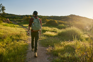 male millennial hiker walking trail in california during sunset