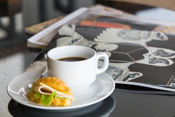 Delicious sanwich and coffee in dish on table
