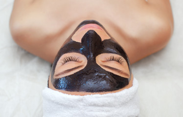 The procedure for applying a black mask to the face of a beautiful woman. Spa treatments and care of the cats in the beauty salon.