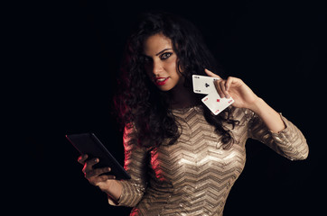 Attractive, sexy young woman holding to aces and tablet in hands, online poker