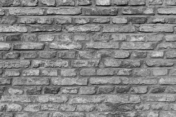 Close-up of an old and aged brick wall texture background in black and white.