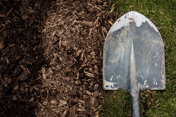 Worn shovel on a background of dirt and grass