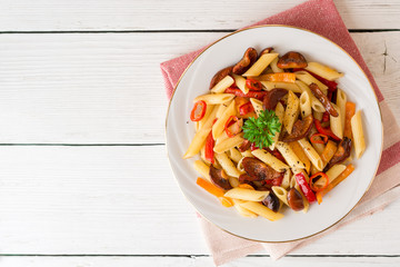 Penne pasta with mushrooms, bell pepper, chilli and parsley on white plate on white wooden background.