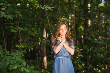 Silence, nature, people and summer concept - Young woman enjoying the green forest.