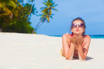woman in bikini relaxing at white sand beach and sending a kiss
